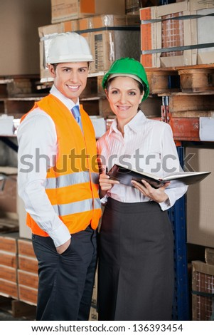 Portrait of two young supervisors with book standing at warehouse