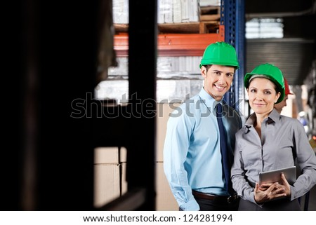 Portrait of two young supervisors with digital tablet smiling together at warehouse - stock photo