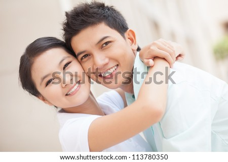 Portrait of two young teenage people embracing and looking at camera