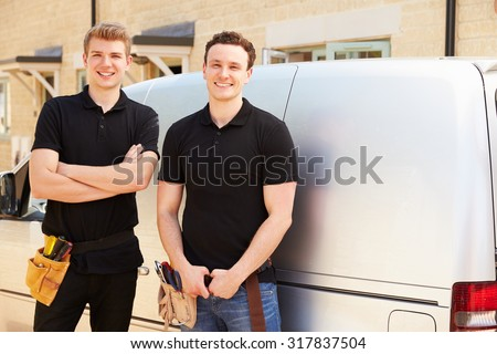 Portrait of two young tradesmen by their van - stock photo