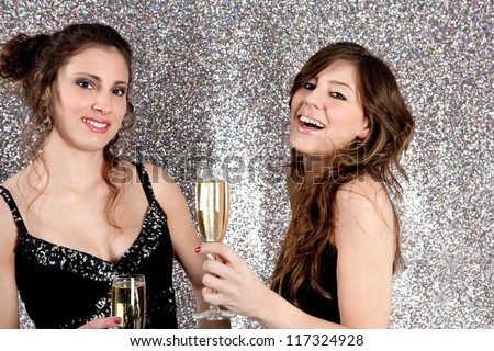 Portrait of two young women toasting with champagne glasses at a Christmas party with a silver glitter background, smiling.