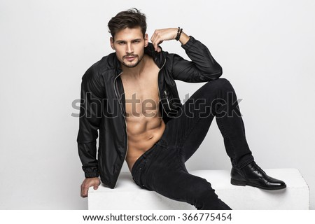 Portrait of undressed handsome man touching his jacket - stock photo