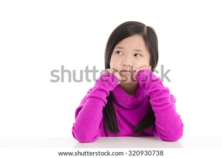 Portrait of unhappy asian girl sitting at desk with hand on chin - stock photo
