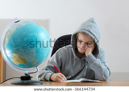 Portrait of unhappy beautiful casual young girl, sitting at desk,  overwhelmed frustrated expression, stuck with tough or stressful study, studio, gray background hood jacket - stock photo