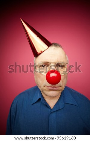 Portrait of unhappy man with a red nose and in a cone cap on fool�s day - stock photo