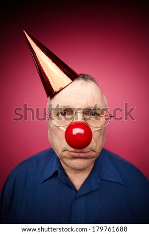 Portrait of unhappy man with a red nose and in a cone cap on fools day - stock photo
