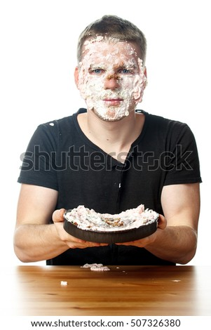 Portrait of unhappy man with cake on his face