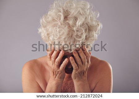 Portrait of unhappy old lady holding he face in hands looking down against grey background. Sad senior woman. - stock photo