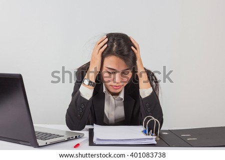 Portrait of unhappy young woman with computer and documents indoors
