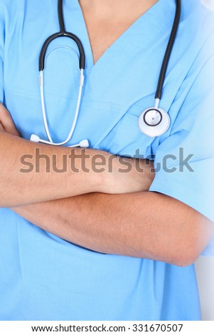 Portrait of unknown male surgeon doctor sitting at the table in hospital office, stethoscope
