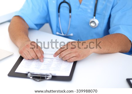 Portrait of  unknown male surgeon doctor with stethoscope, sitting at the table in hospital office, hands above medical history - stock photo