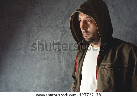 Portrait of unshaven man wearing jacket with hoodie. - stock photo