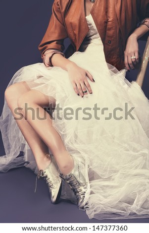 portrait of untraditional bride with tulle wedding dress wearing sequin shoes and leather jacket sitting against a purple background with retro effect  - stock photo