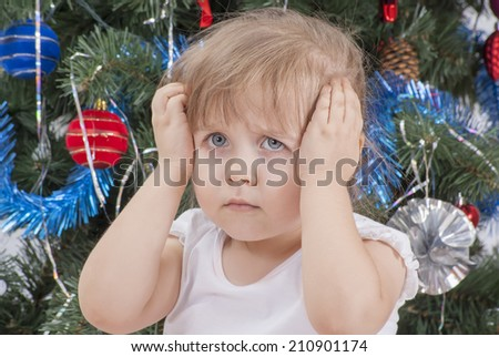 Portrait of upset and distraught screaming little girl in white T-shirt near the Christmas tree. Christmas time, New Year. - stock photo