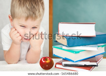 Portrait of upset boy sitting at desk with books holding his head