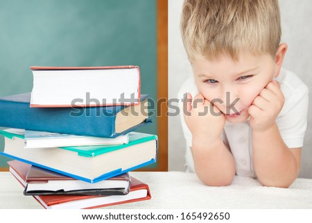 Portrait of upset boy sitting at desk with books holding his head - stock photo