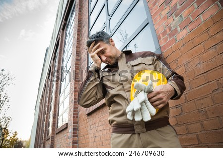 Portrait Of Upset Male Worker With Hardhat Standing In Front Of Brickwall - stock photo
