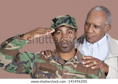 Portrait of US Marine Corps soldier with father saluting over brown background - stock photo
