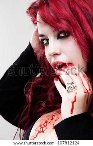 Portrait of vampire bloody woman with yellow cat eyes - stock photo