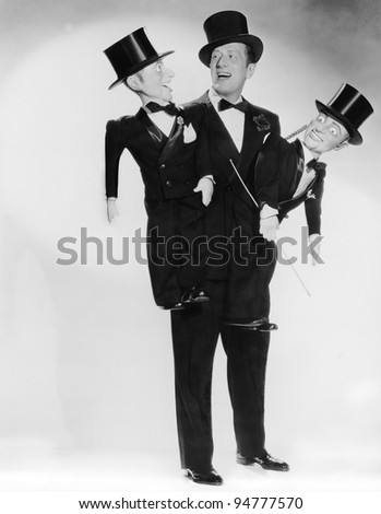 Portrait of ventriloquist with two dummies - stock photo