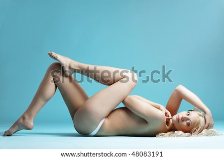 Portrait of very beautiful naked woman over blue - stock photo