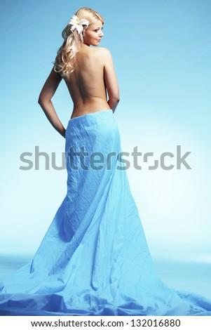 Portrait of very beautiful woman wearing long dress over blue - stock photo