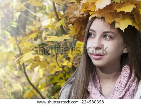 Portrait of very beautiful young girl in autumn park