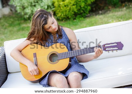 Portrait of very handsome teenager playing guitar in her garden - stock photo