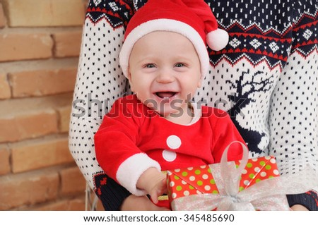 portrait of very happy cute little baby boy in Santa suit with gift sitting on mother's knees, happy holiday concept - stock photo