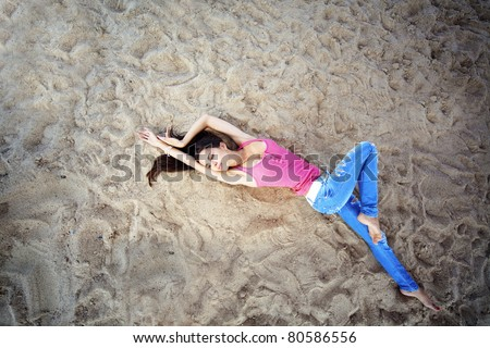 Portrait of very pretty beautiful girl lying on sand - stock photo