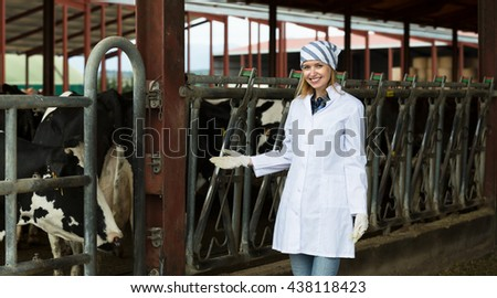 Portrait of veterinary technician with dairy cattle in farm