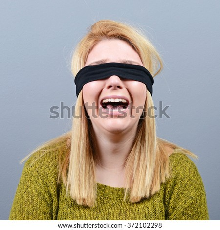 Portrait of victim of abuse and domestic violence blindfolded against gray background - stock photo