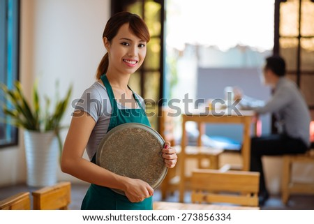 Portrait of Vietnamese beautiful waitress with a tray standing in a cafe - stock photo