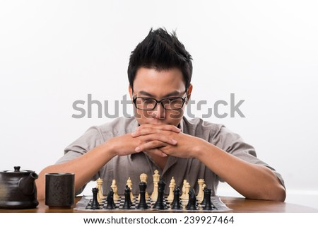 Portrait of Vietnamese chess player thinking about next move - stock photo