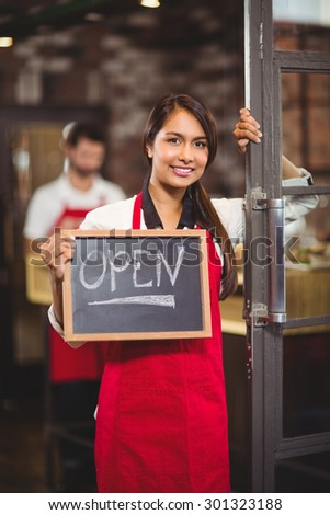 Portrait of waitress showing chalkboard with open sign at coffee shop - stock photo