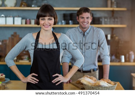 Portrait of waitress standing with hand on hip in cafe