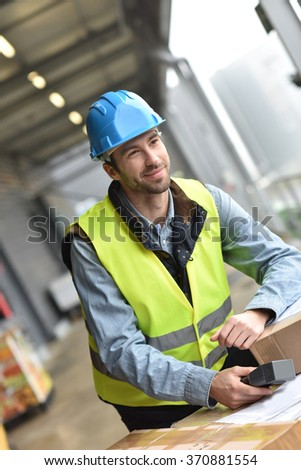 Portrait of warehouseman scanning merchandise on dock