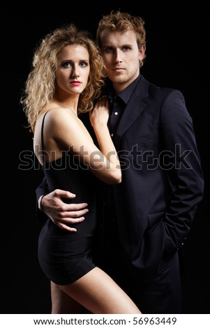 portrait of well-dressed blonde couple on black. - stock photo