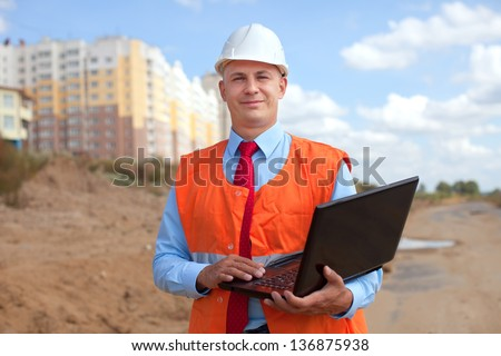 Portrait of white-collar worker wearing protective helmet works on the building site - stock photo