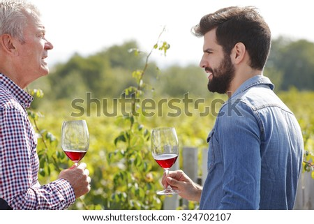 Portrait of winemakers consulting at vineyard. Senior owner of vinery and young professional man tasting red wine and working together. Small business.