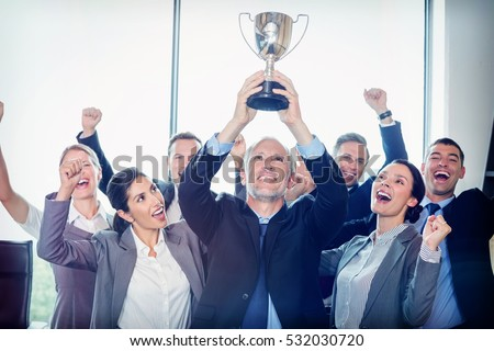 Portrait of winning business team with an executive holding a gold trophy