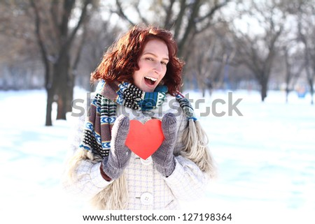 Portrait of winter girl with the red heart in park - stock photo