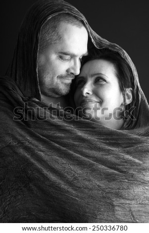 Portrait of woman and man in love sharing a shawl, monochrome - stock photo