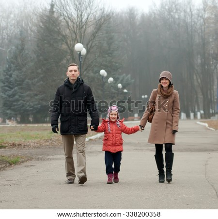Portrait of   woman and   man with   child in autumn day. - stock photo