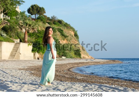 Portrait of woman at the beach wearing long coral dress