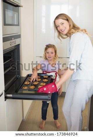 Portrait of woman baking cookies with daughter in kitchen