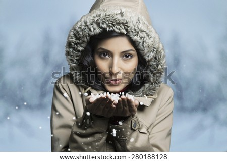 Portrait of woman blowing snow from her hands - stock photo