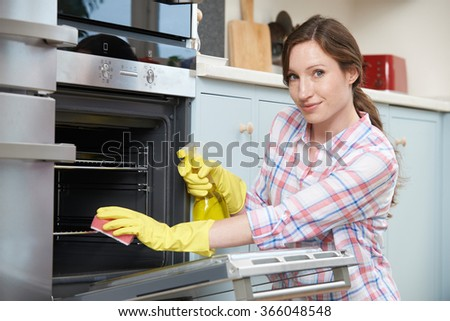 Portrait Of Woman Cleaning Oven At Home - stock photo