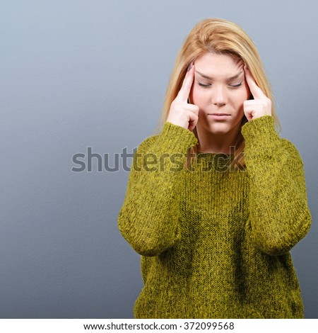 Portrait of woman concentrating against gray background - stock photo