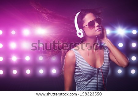 Portrait of woman dj enjoying music on headphones and nightclub lights